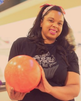 smiling woman holding a pink bowling ball