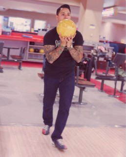 man in bowling pose holding a ball in hand